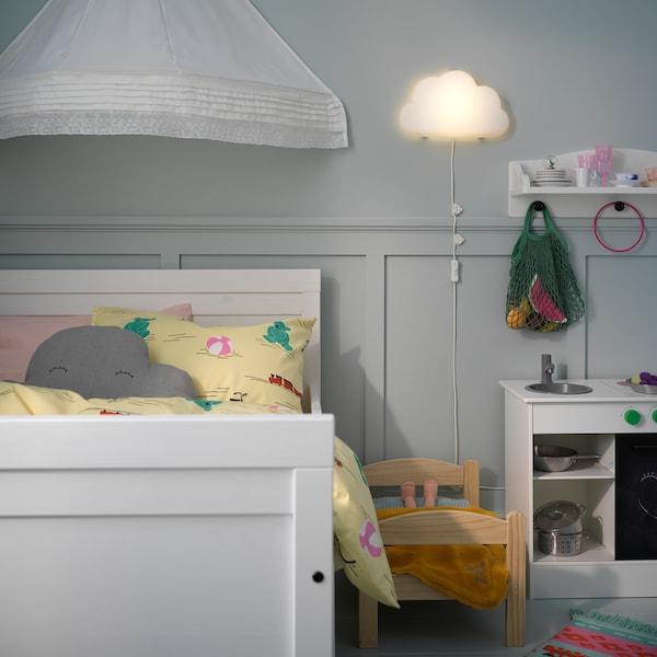 Lámpada de parede LED UPPLYST con forma de nube que dá unha luz cálida, xunto a unha cama infantil branca.