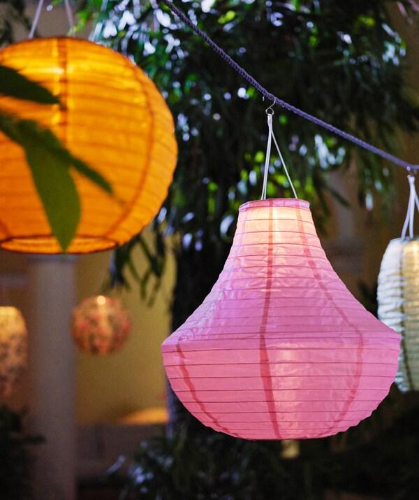 Lampade a sospensione LED a energia solare SOLVINDEN di varie forme e colori, appese a diverse altezze in un giardino lussureggiante - IKEA