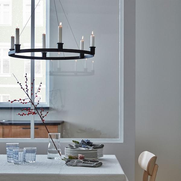 Lámpara de araña VÄRMER de aluminio con velas encendidas sobre una mesa de comedor minimalista con platos y vasos.