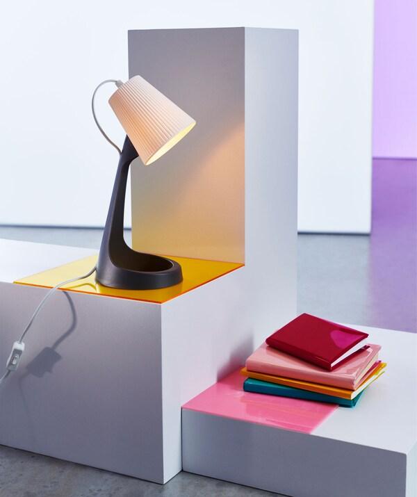 Lámpara de mesa de plástico sobre un soporte encima de unos libros.