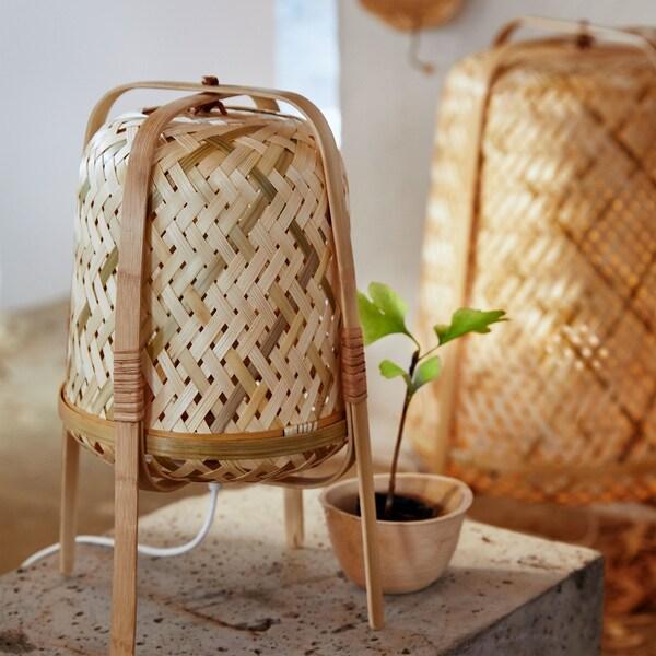 Lámpara de mesa KNIXHULT sobre cuatro patas de madera curvadas que encierran su figura cilíndrica tejida en varios tonos de bambú.