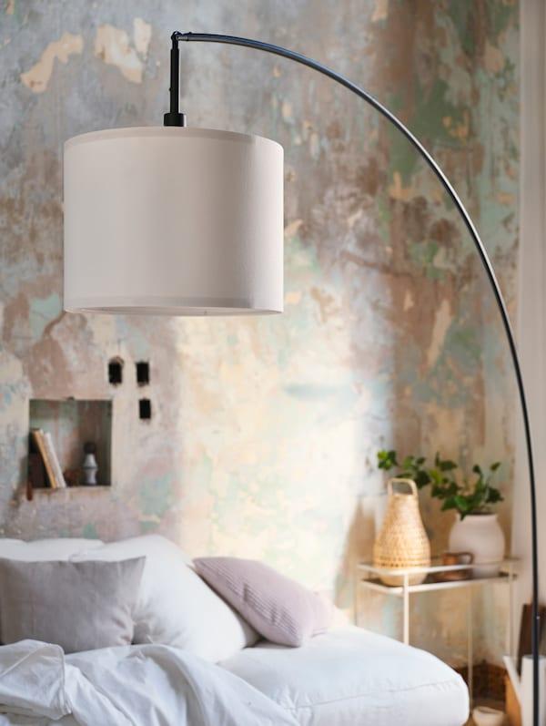 Lámpara de pie arqueada en negro con una pantalla blanca. De fondo se ve un soporte para plantas de color crema.