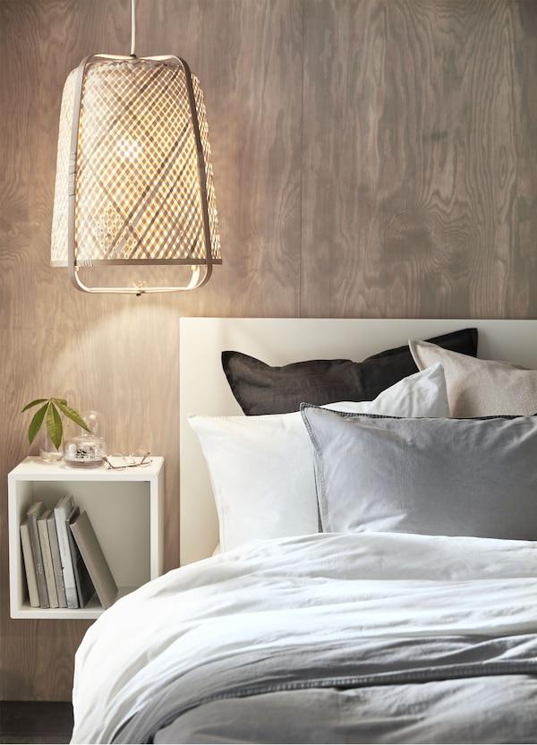 Lámpara de techo de bambú IKEA KNIXHULT que ilumina con luz suave, junto a una cama.