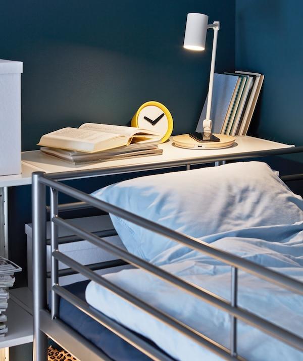 Lámpara de trabajo RIGGAD iluminando una cama y un teléfono cargándose.