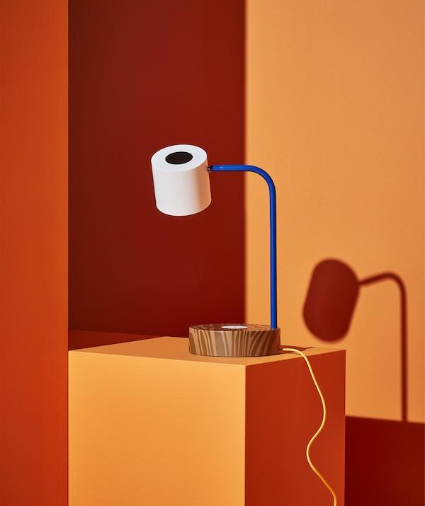 Lampe de bureau: base brune, bras bleu et abat-jour blanc, posée sur une marche orange.