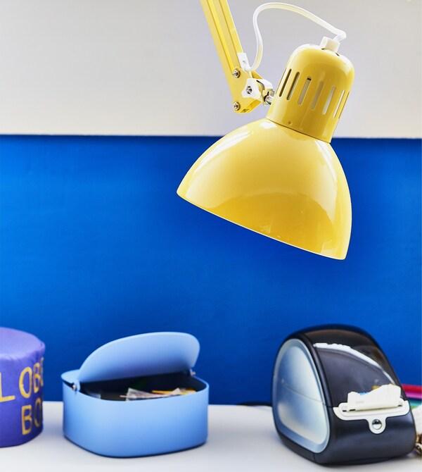 Lampe de bureau jaune sur fond de mur bleu.