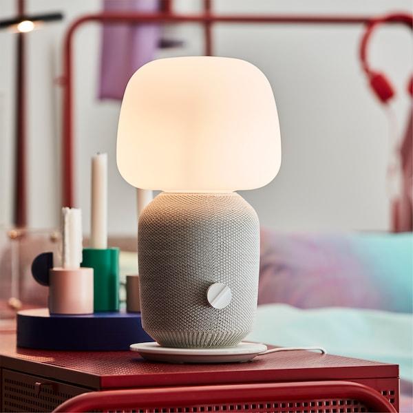 Lampe de table IKEA SYMFONISK en blanc, posée sur une commode rouge, dans une chambre à coucher.