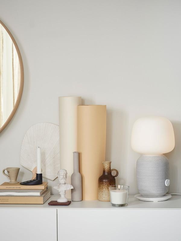 Lampe de table SYMFONISK blanche et haut-parleur sur un buffet avec des objets décoratifs.