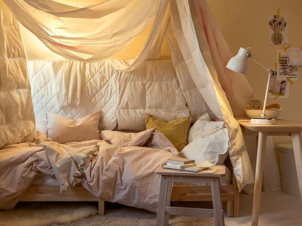 Lampe de travail HEKTAR blanche et lit drapé de linge de lit varié dans les tons de blanc, de jaune et de rose.