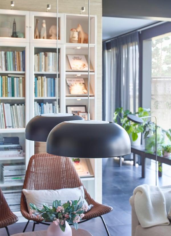 Lămpi NYMÅNE, negru antracit, de la IKEA suspendate deasupra unei măsuțe de cafea într-o cameră de zi.