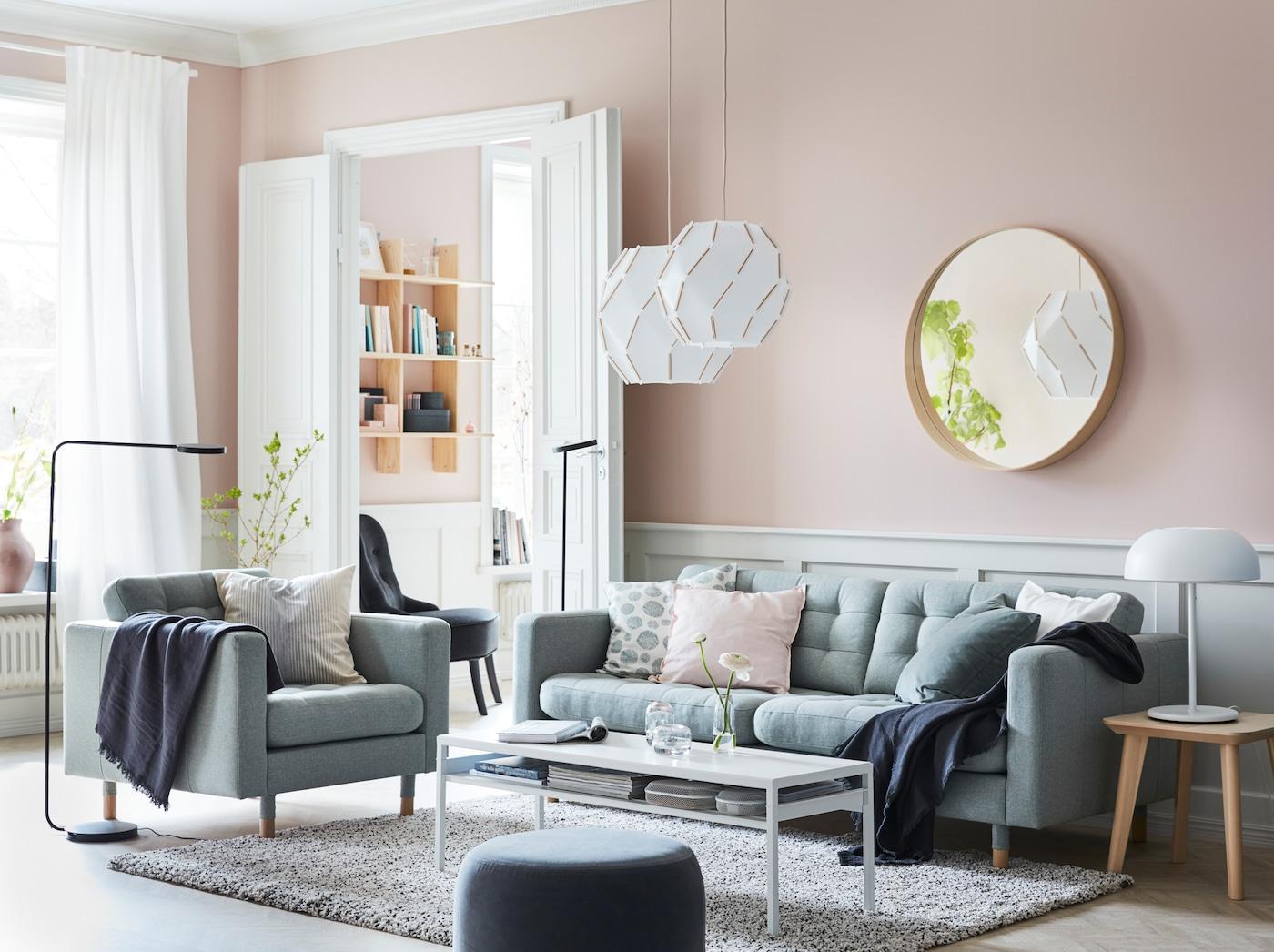 LANDSKRONA light green sofa sectional, SJÖPENNA pendant lamps and black YPPERLIG standing lamps in a pink walledl living room.