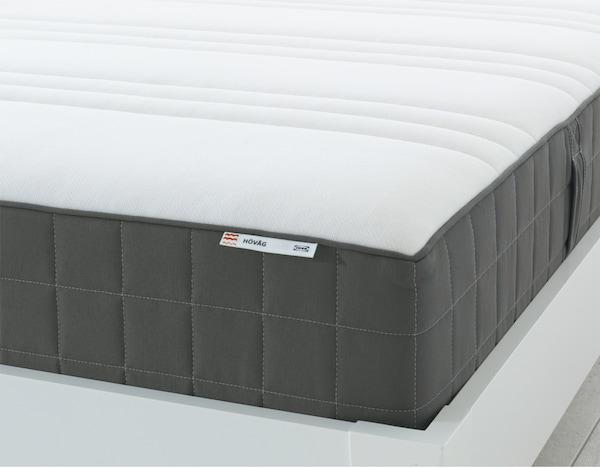 L'angolo di un materasso a molle insacchettate HÖVÅG di IKEA, con parte superiore bianca e lati grigio scuro.