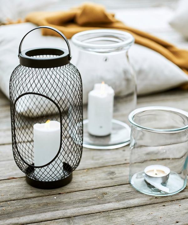 Lanterne en maille noire métallique avec bougie à côté de deux bocaux en verre avec bougies, à côté d'un coussin et d'un jeté jaune sur la terrasse.