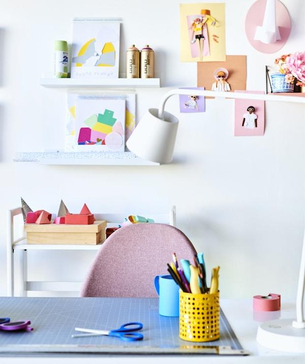 Lapiceros sobre un escritorio con una lámpara de escritorio blanca, una silla rosa y creaciones artísticas sobre repisas para cuadros en la pared de atrás.