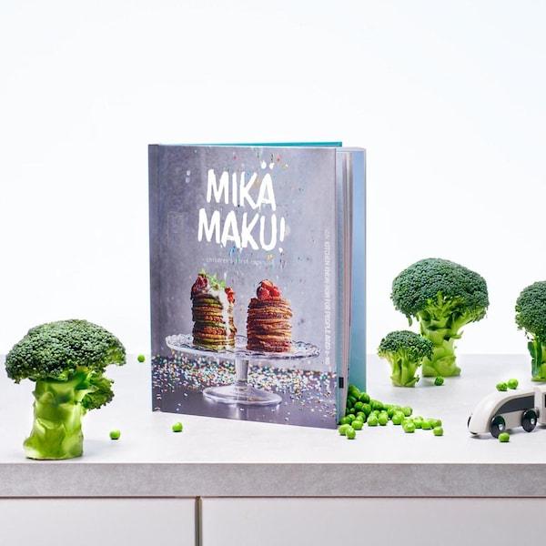 Lapsen oma ruokakirja Mikä maku!, kannessa pino lettuja ja niiden päällä metsämarjoja.