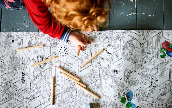 Lapsi värittää värityspaperia maalatun puulattian päällä.