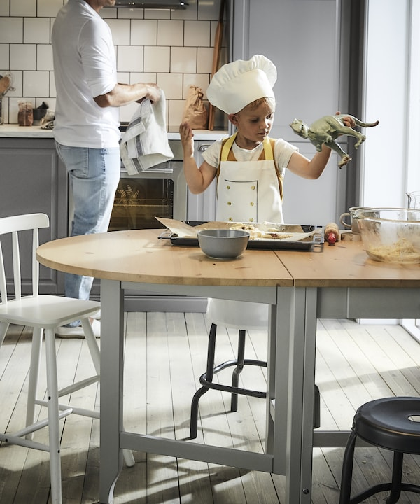 Lapsi valmistaa taikinaa GAMLEBY ruokapöydän päällä.