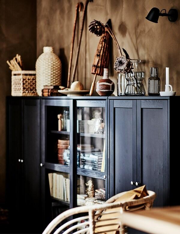 Large armoire HAVSTA de couleur foncée remplie d'objets décoratifs faits de matériaux naturels dans un coin d'unsalon.