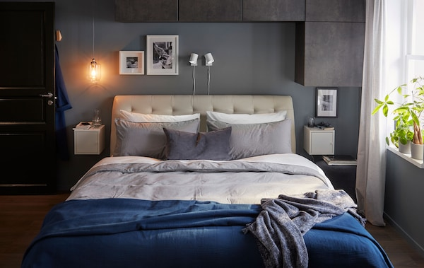 Large double bed in a bedroom with a grey-blue colour scale. Wall-mounted cabinets over and beside the bed, plants in window.