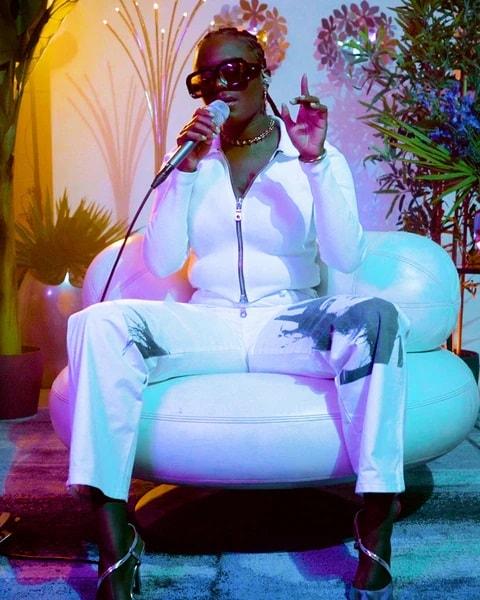 L'artiste Amaarae dans un fauteuil blanc, vêtue de vêtements blancs et chantant dans un micro.