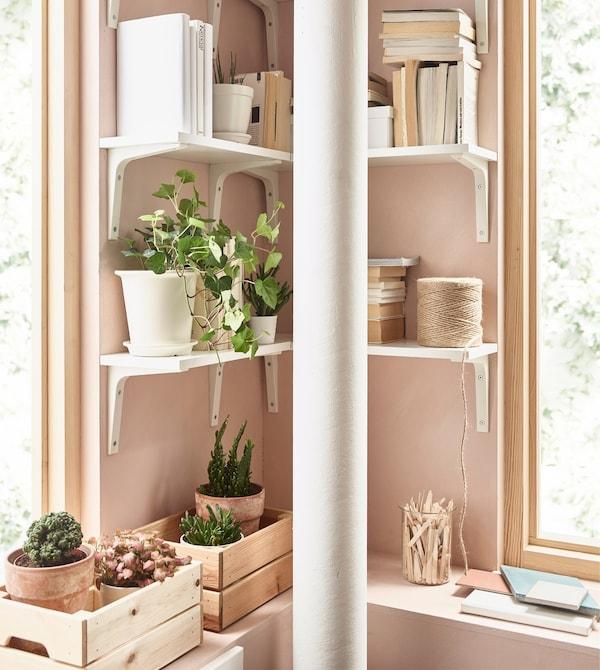 Las baldas EKBY ÖSTEN y los soportes EKBY STÖDIS blancos crean un almacenaje en esquina en un salón rosa.