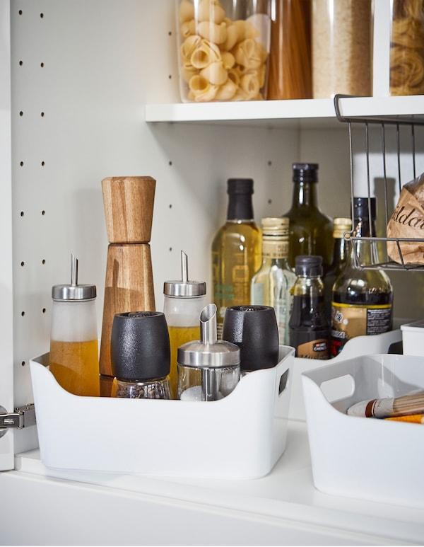 Las cajas de plástico liso IKEA VARIERA en blanco, con asas fáciles de agarrar, son soluciones para evitar los derrames de las botellas altas de aceite y salsas.