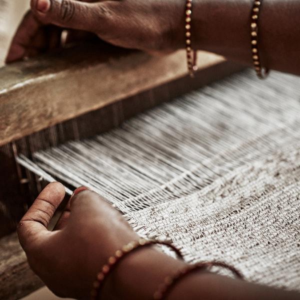Las manos de una trabajadora tejiendo para confeccionar una alfombra en un telar.
