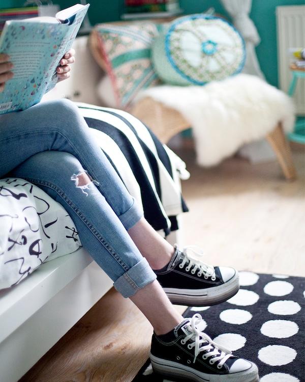 Las piernas de una persona sentada en una cama, con alfombras y tejidos monocromáticos en la habitación.