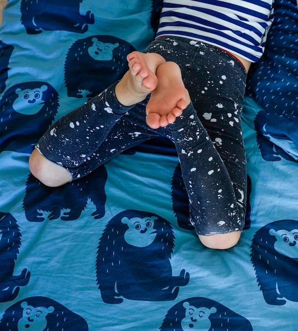 Las piernas un niño que está sobre la cama con ropa de cama con estampado animal de color azul.