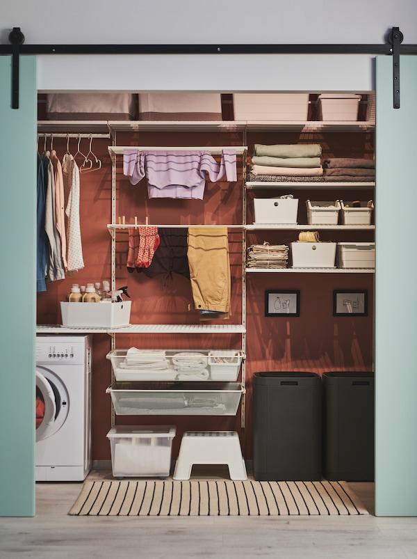 Las puertas verdes se abrieron para revelar una pared dispuesta para ropa, estanterías BOAXEL y una lavadora.