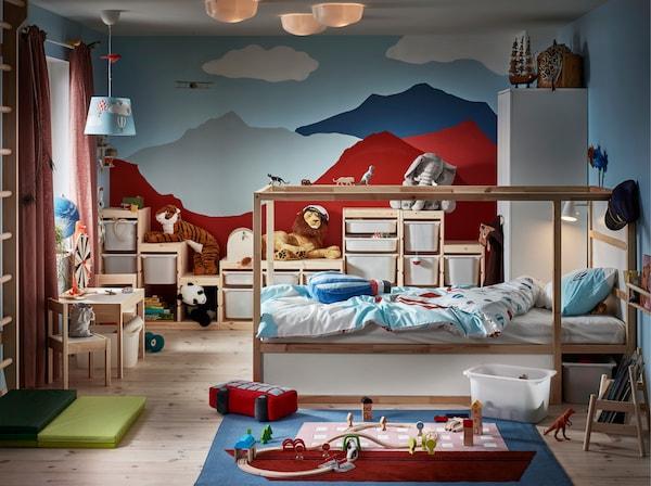 Lastenhuoneessa on käännettävä KURA-sänky mäntyä, seinään on maalattu värikkäitä vuoria ja lattialla on matto.