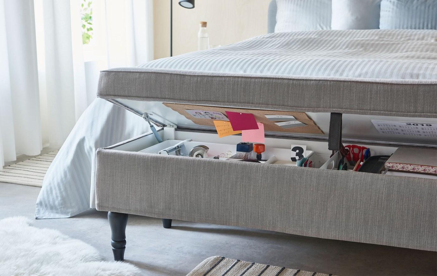 Látkou potažená lavice s úložným prostorem před postelí, prostor využitý na výtvarní potřeby