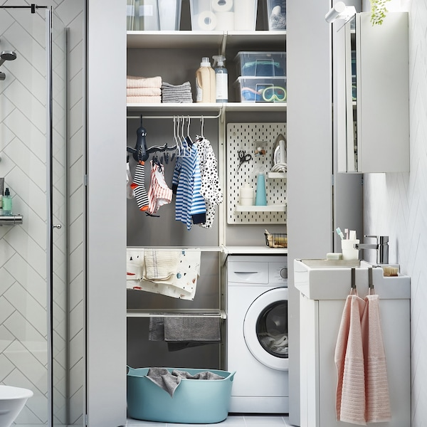 Laundry area with washing machine, an ALGOT drying rack, a white SKÅDIS pegboard, and clear SAMLA boxes on shelves.
