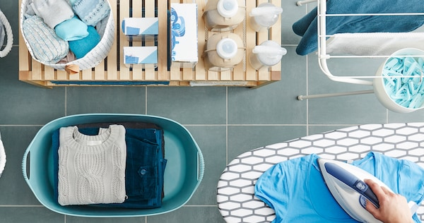 Laundry featuring a person ironing a blue shirt, a laundry basket with folded laundry and bench with various detergents
