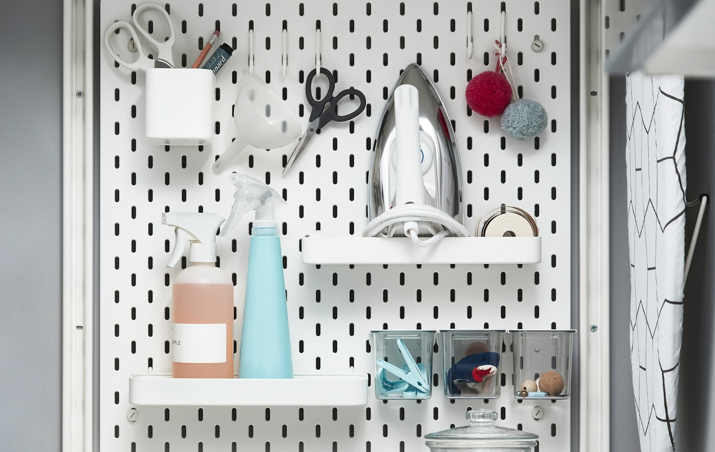 Laundry-related items stored on shelves, in pots and on hooks on a white pegboard.