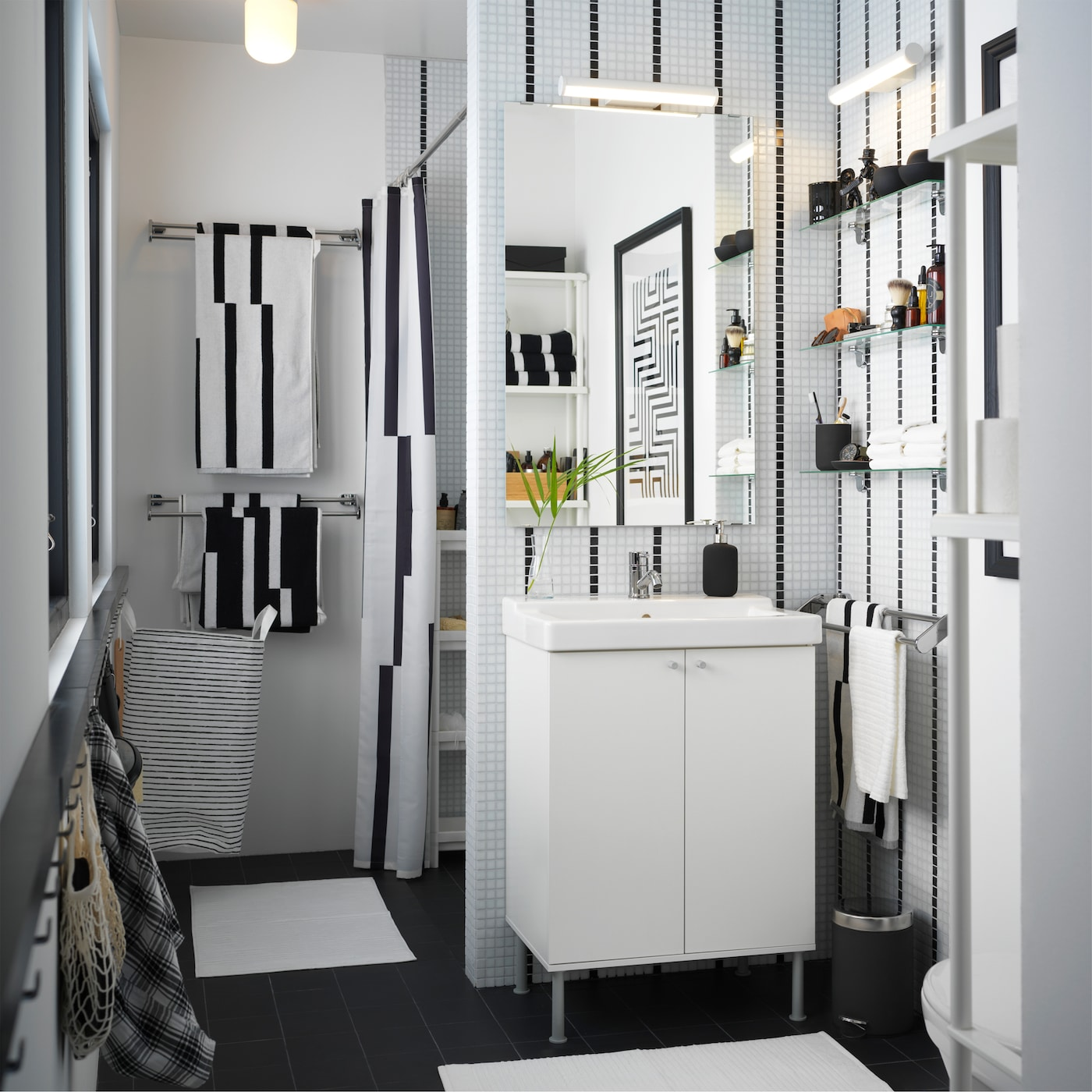 Lavabo blanc, serviettes et rideau de douche rayé dans une petite salle de bains en noir et blanc.
