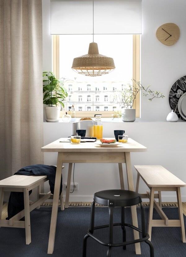 Lavica IKEA NORRÅKER so svetlého dreva a čierna stolička NORRÅKER použité ako jedálenský nábytok vedľa okna v kuchyni.