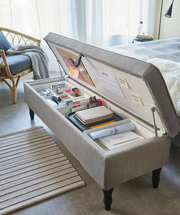 Lavica s úložným priestorom a textilným poťahom na konci postele s potrebami do domácej kancelárie vo vnútri.