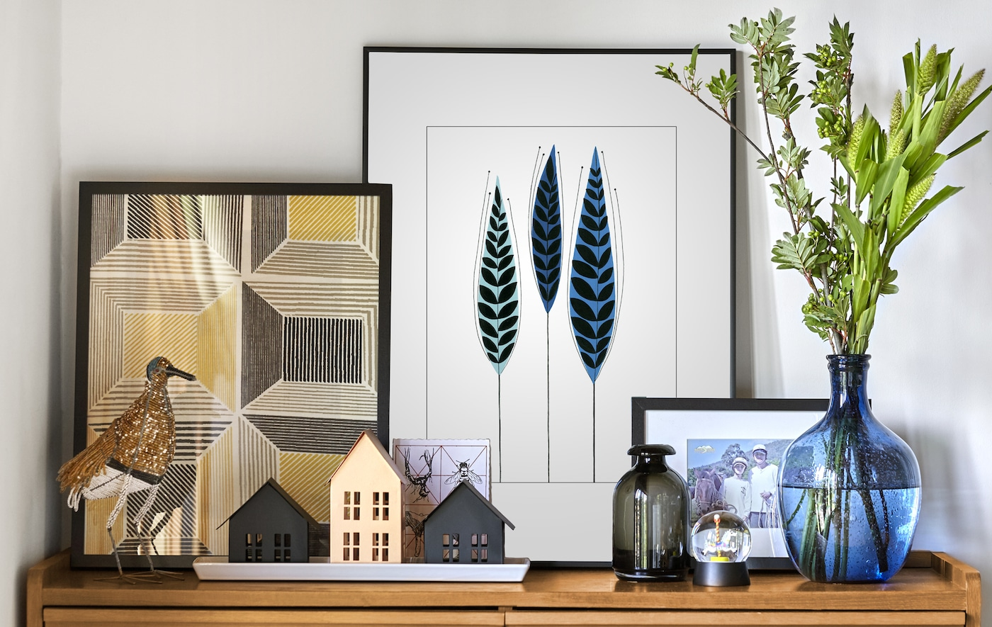 Layered pictures, ornaments, and vases on a natural wood cabinet in a white room.
