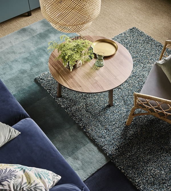 Layered rugs in shades of green under a round, wood coffee table in a living room.