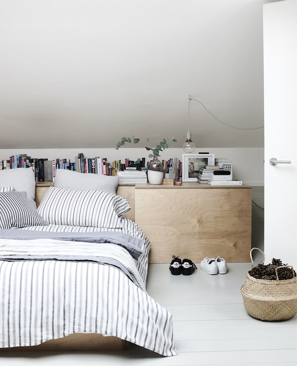 Layers of striped bed textiles on a low bed for two in a minimal bedroom with a wood chest of drawers.