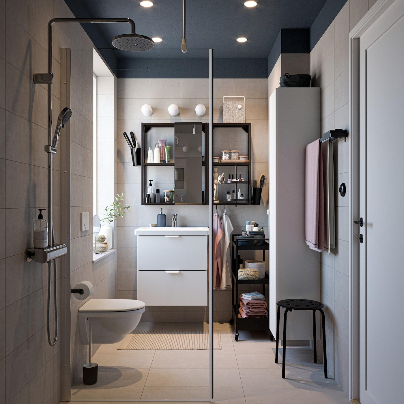 Łazienka z czarnymi i białymi meblami, chromowanym zestawem prysznicowym, jasnoróżowymi ręcznikami i szklaną ścianką kabiny prysznicowej.