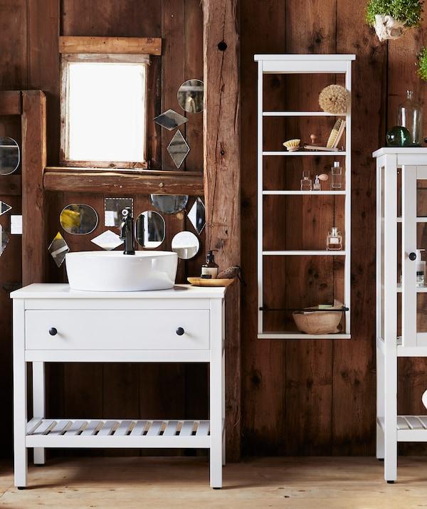 Łazienka ze ścianami z ciemnego drewna, białą szafką pod umywalkę z szufladą i białymi półkami na ścianie.