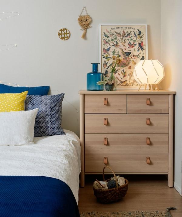 Le bord d'un lit avec linge de lit bleu et blanc à côté d'une commode dans une chambre blanche.