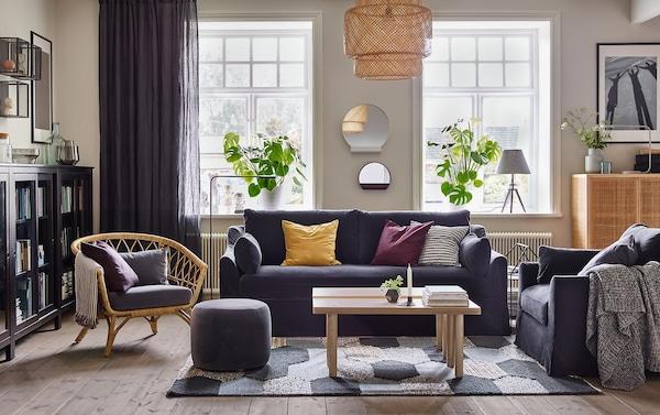 Le canapé et le fauteuil spacieux et confortables FÄRLÖV en Djuparp gris foncé constituent des pièces centrales dans un salon gris et beige.