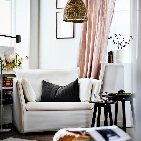 Le coin d'un séjour lumineux et ensoleillé avec un fauteuil BACKSÄLEN blanc à côté de tables gigognes et d'un rideau rose.