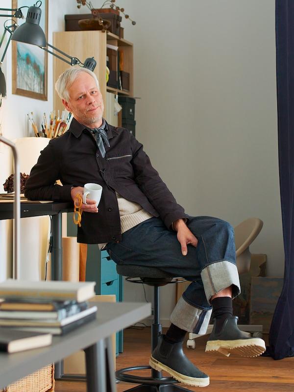 Le designer Hans Blomquist assis sur un tabouret dans une pièce claire, une tasse en main.