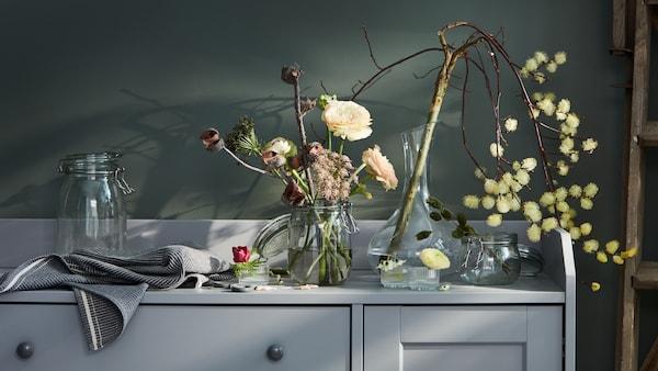 Le dessus d'un buffet HAUGA gris décoré de divers arrangements floraux dans des vases et une carafe STORSINT.