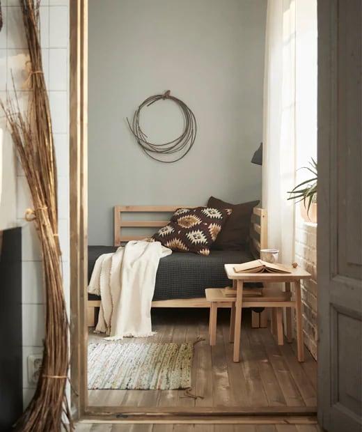 Le linge de lit de couleur neutre ajouté au lit d'appoint TARVA en bois naturel habillent joliment cette pièce multifonction, et le petit tapis assure le confort des pieds.