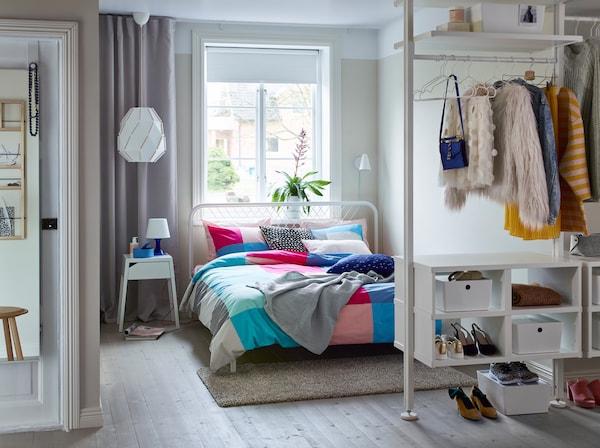 Le lit, la table de chevet et la commode à 4 tiroirs de la collection TRYSIL en brun foncé meublent joliment cette pièce chaleureuse et invitante.